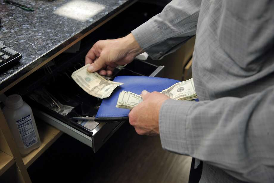 Dave McCullick, General Manager at Magnolia Wellness, a medical marijuana dispensary in Oakland, Calif., removes cash from a register near the end of business hours on Wednesday, November 30, 2016. Cash is how business is conducted at Magnolia. Like many businesses working in the cannabis industry, Magnolia Wellness has to deal with a lack of access to formal banking services. However, a special bank may soon open up in oakland to fill this void. Photo: Carlos Avila Gonzalez, The Chronicle