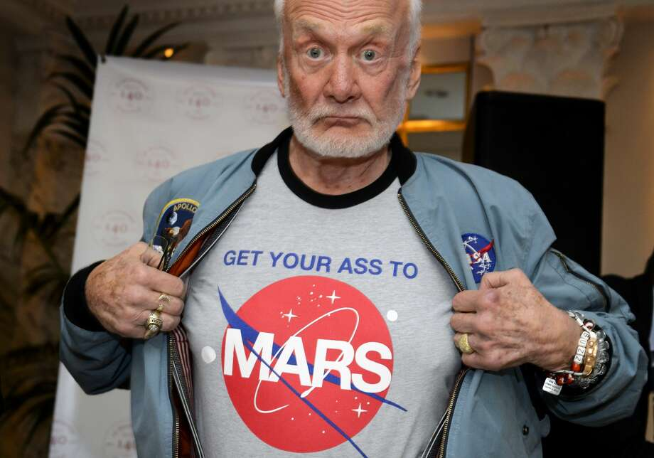 "Former NASA astronaut Buzz Aldrin shows the t-shirt he wears promoting Mars exploration on November 12, 2015 in Geneva. Aldrin attended a press conference alongside Soviet cosmonaut Alexei Leonov and Swiss astronaut Claude Nicollier on the eve of a conference in Lausanne entitled ""The Moon Race"". Photo: FABRICE COFFRINI/AFP/Getty Images"