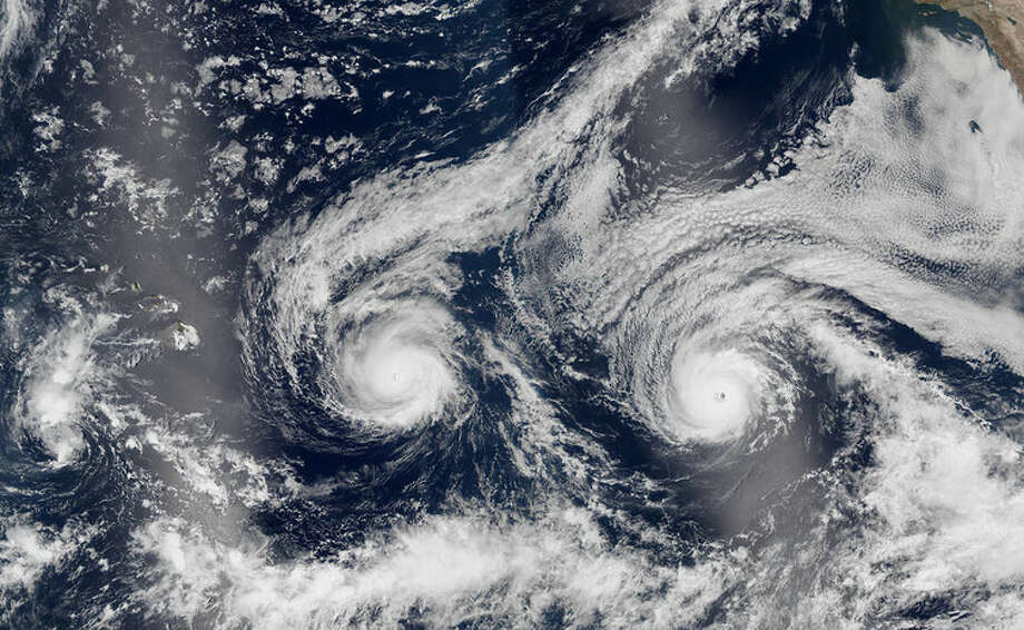 In an image from the Suomi NPP satellite,  Hurricanes Madeline and Lester, both hovering between Categories 3 and  4, bear down on Hawaii on Aug. 29, 2016. Photo:  NASA Earth Observatory