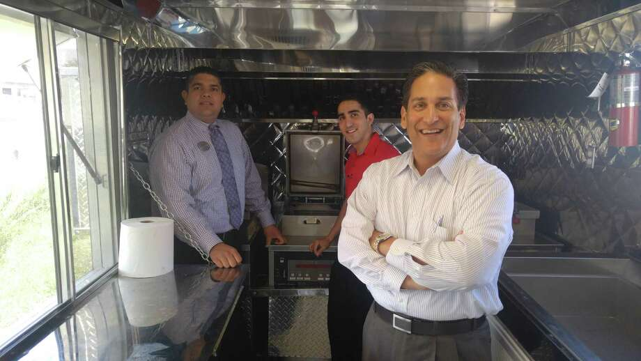 Chick-fil-A franchisee Jesse Chaluh, from right, leadership director David Chaluh and director of operations Jesus Baca check out the new Chick-fil-A food truck that will roll out in Houston in time for the Super Bowl. Photo: Ken Hoffman