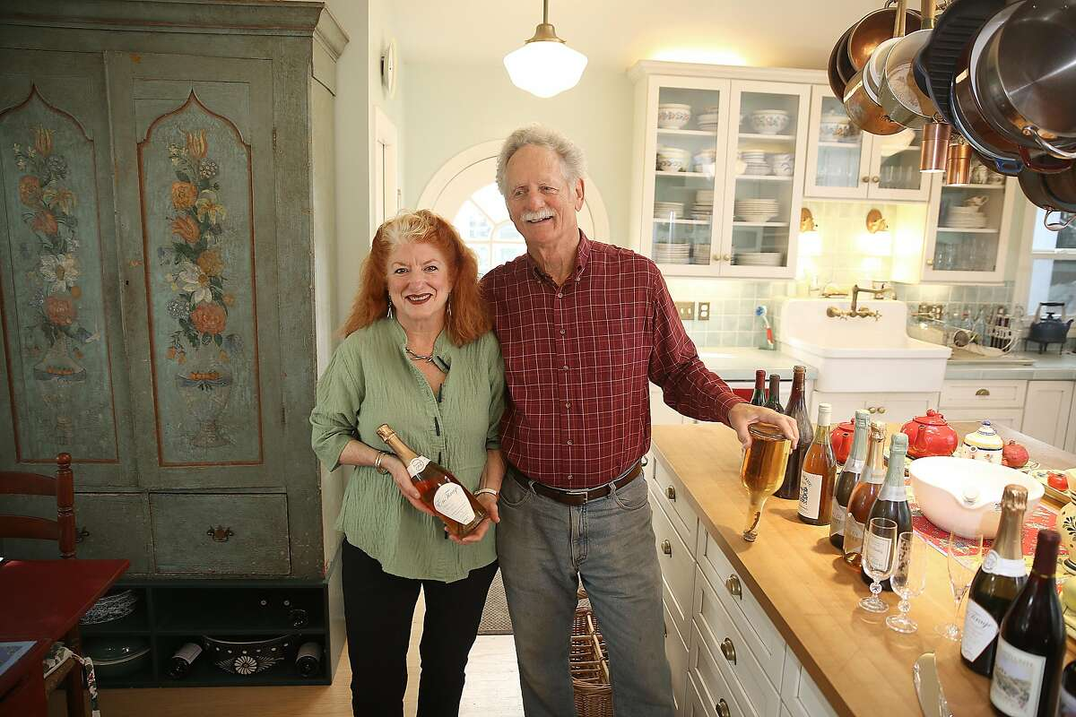 Kay Baumhefne (left) carries a 1990 bottle of En Tirage and Don Baumhefne (right) holds his first bottle of champagne on Monday, November 11, 2016, at home in Petaluma, Calif.