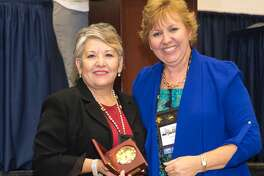 Anita Flores (left), migrant recruiter for Plainview ISD, accepts the 2016 Recruiter Service Award from Linda Aranda, president for the Association for Migrant Educators of Texas.