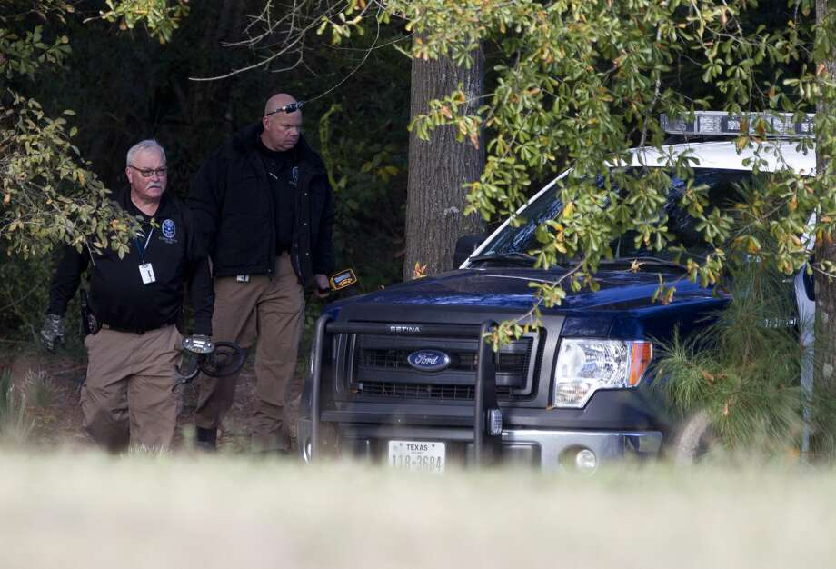 Investigators with the Conroe Police Department's crime scene unit carry gear out of a crime scene involving the recovery of human skeletal remains near Northside Baptist Church Thursday, Dec. 1, 2016, in Conroe. Photo: Jason Fochtman/Houston Chronicle