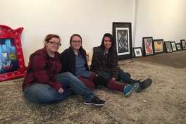 Cynna Guerrero, Callie Deming and Andrea Valencia take a break from hanging their works of art for the First Friday show at Kamiposi.