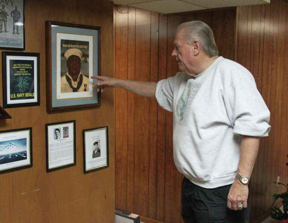 Dale Everitt points out various pictures depicting veterans of World War II, including Dorie Miller. Miller served on the USS West Virginia as a cook during the attack on Pearl Harbor and took control of one of the ship's guns to help fend off Japanese aircraft. He is the first black American to be awarded the Navy Cross. Photo: Jacob McAdams