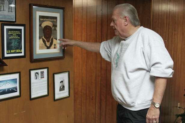 Dale Everitt points out various pictures depicting veterans of World War II, including Dorie Miller. Miller served on the USS West Virginia as a cook during the attack on Pearl Harbor and took control of one of the ship's guns to help fend off Japanese aircraft. He is the first black American to be awarded the Navy Cross.