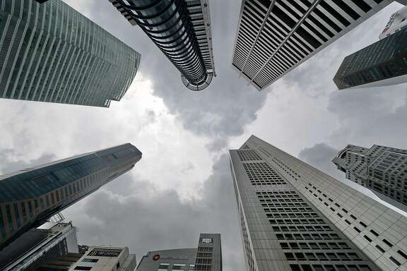 Dark clouds loom over the skyscrapers in Raffles Place, the financial district of Singapore, on November 11, 2016. / AFP PHOTO / ROSLAN RAHMANROSLAN RAHMAN/AFP/Getty Images