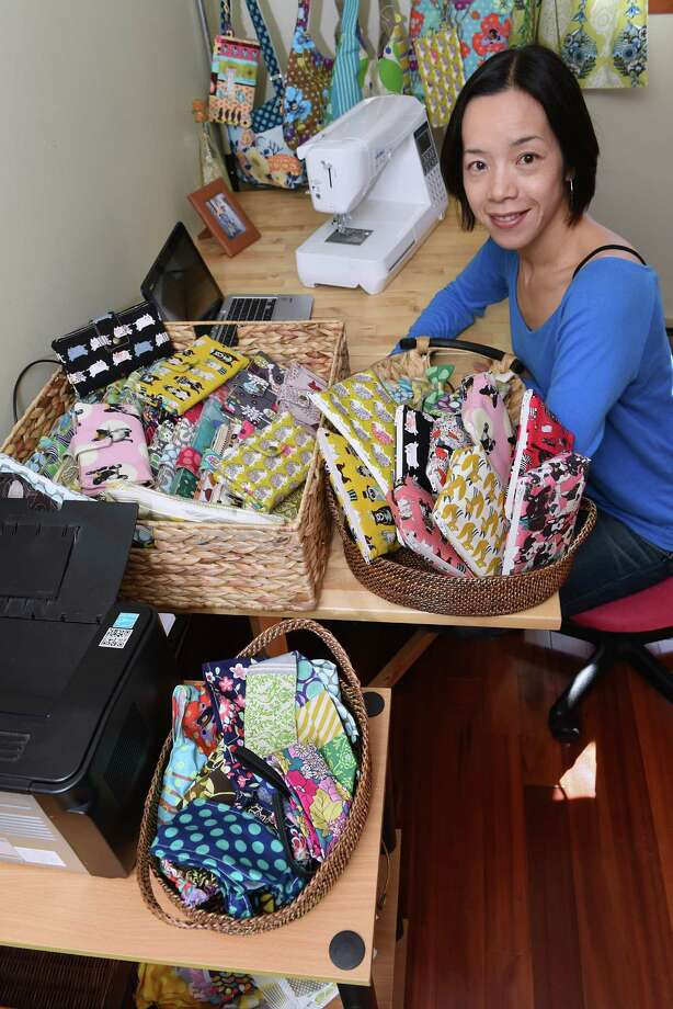 Yuko Stano sits in the room in her home where she makes homemade wallets to sell on Etsy on Wednesday, Oct. 19, 2016 in Loudonville, N.Y. (Lori Van Buren / Times Union) Photo: Lori Van Buren / 20038443A