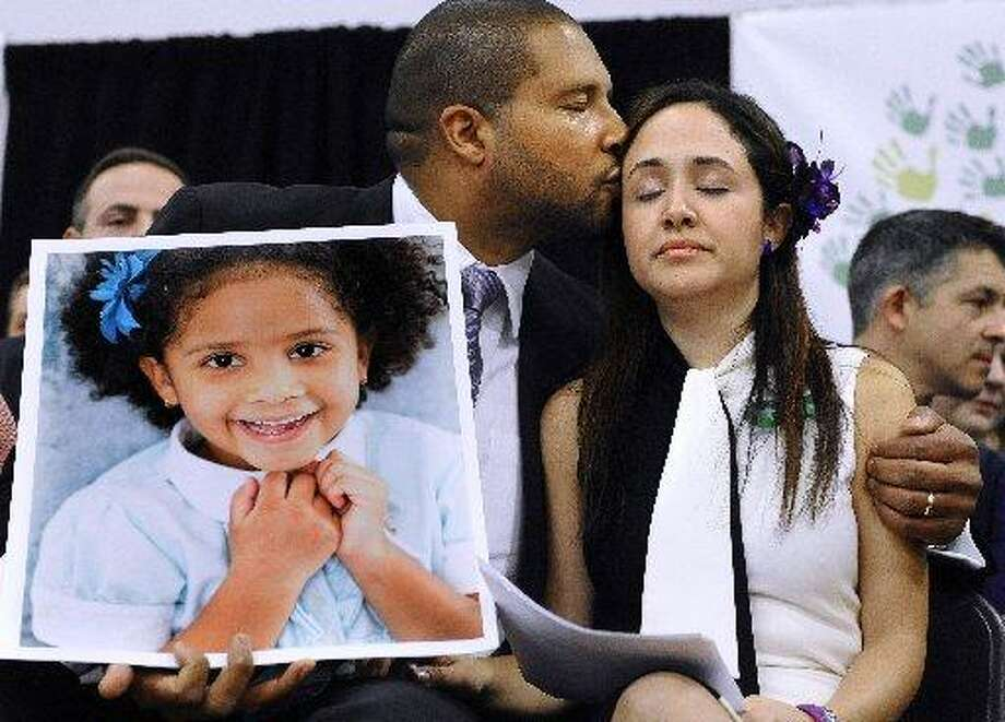 Jimmy Greene, left kisses his wife Nelba Marquez-Greene as he holds a portrait of their daughter, Sandy Hook School shooting victim Ana Marquez-Greene, at a 2013 news conference. Photo: Jessica Hill / Associated Press