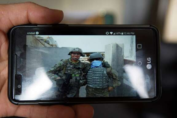 Samir Kohistani shows a picture of himself and a U.S. Army soldier he worked with as a translator in his native Afghanistan, Monday, Nov. 28, 2016, in Houston. He had to hide his identity when working because of the danger associated with his job. After earning his legal entry to the United States, Kohistani is now living in an apartment with several other former translators and working at a print shop. Kohistani is hoping to either study to be a nurse or join the U.S. Army in order to give back to the country he says gave so much to him.