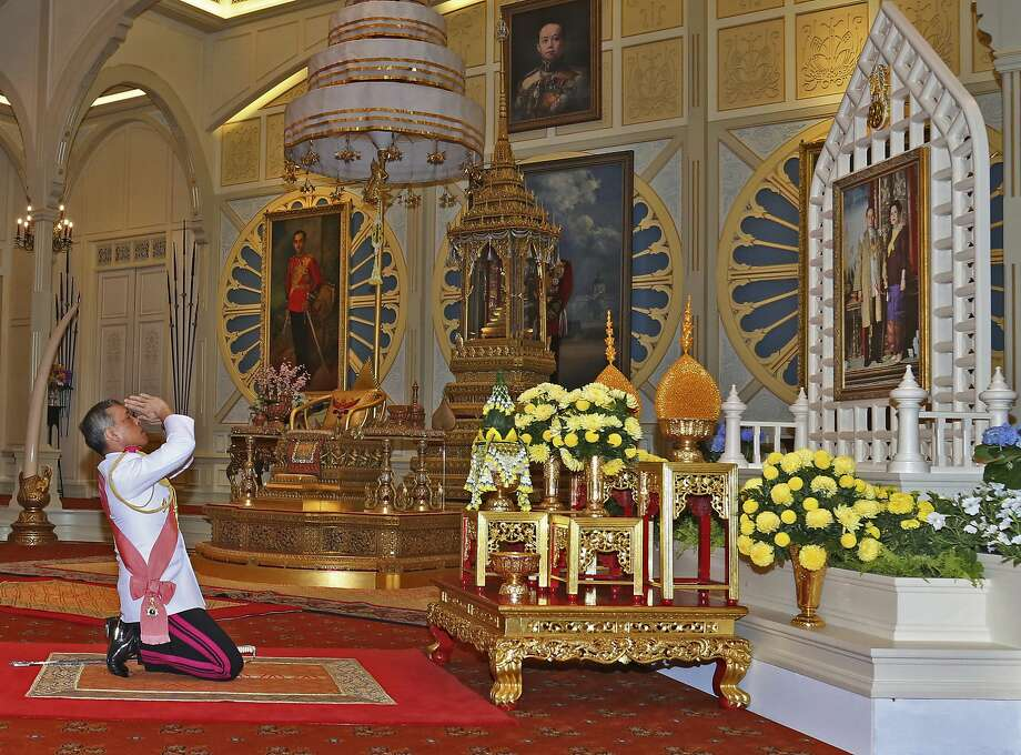 The new king, Maha Vajiralongkorn Bodindradebayavarangkun, pays respects to a portrait of his late father and mother at the Dusit Palace in Bangkok. Photo: Associated Press