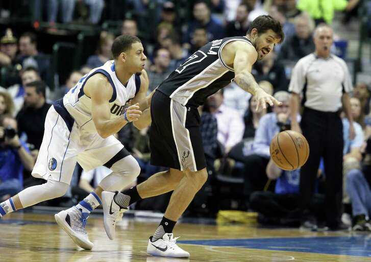 Spurs guard Nicolas Laprovittola reaches for the ball against Mavericks guard Seth Curry during the first half in Dallas on Nov. 30, 2016.