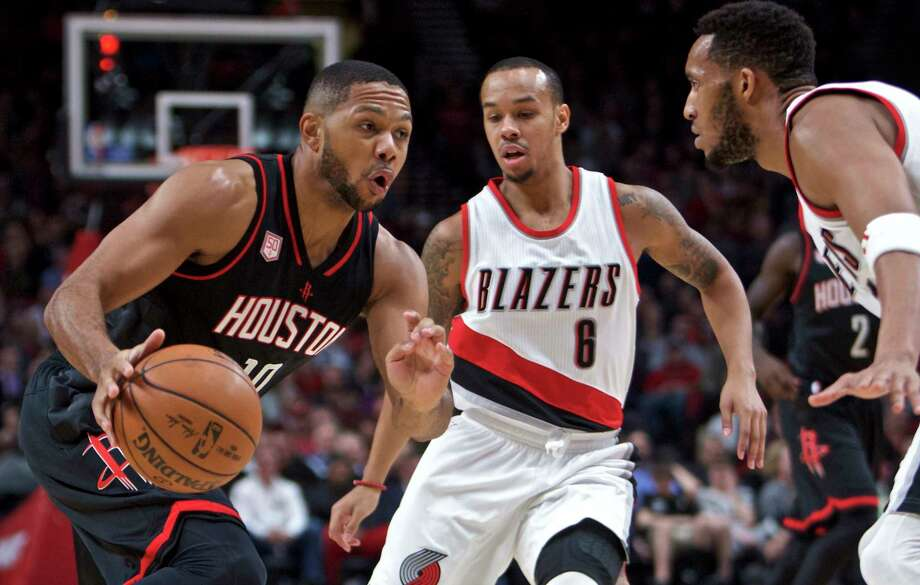 Houston Rockets guard Eric Gordon, left, dribbles past Portland Trail Blazers guard Shabazz Napier, center, and guard Evan Turner, right, during the first half of an NBA basketball game in Portland, Ore., Sunday, Nov. 27, 2016. (AP Photo/Craig Mitchelldyer) Photo: Craig Mitchelldyer, FRE / FR170751 AP