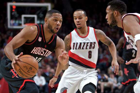 Houston Rockets guard Eric Gordon, left, dribbles past Portland Trail Blazers guard Shabazz Napier, center, and guard Evan Turner, right, during the first half of an NBA basketball game in Portland, Ore., Sunday, Nov. 27, 2016. (AP Photo/Craig Mitchelldyer)