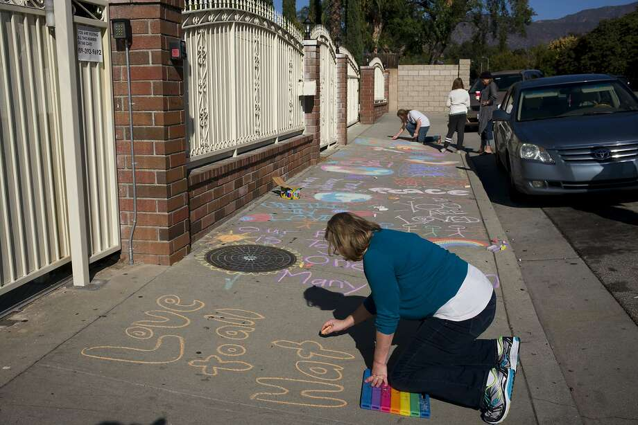Karen Fagan, joined by her daughters, Kate and Elizabeth chalk messages on the sidewalk outside an Islamic center in Pomona, Calif., to show their support for Muslim communities. Fagan's ex-husband and her two daughters' father, Harry Bowman, was killed in the Dec. 2, 2015, terror attack at the Inland Regional Center in San Bernardino, Calif. (AP Photo/Jae C. Hong) Photo: Jae C. Hong, Associated Press