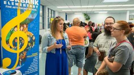 School staff discusses magnet options with parents at a school choice fair in September at Westbury High School.