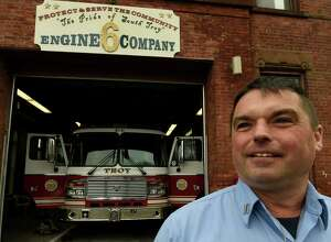 Retiring Captain Mike Spinelli stands beneath the sign that he made that hangs above the engine bay on Thursday, Dec. 1, 2016, at the Engine 6 quarters in Troy, N.Y. Spinelli retired on Thursday after 30 years with Troy Fire Department. (Skip Dickstein/Times Union)