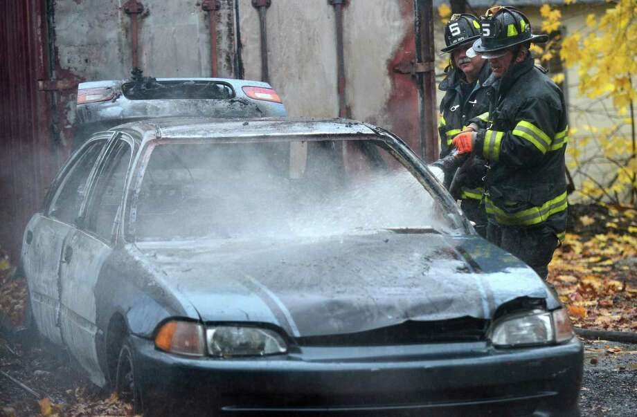Norwalk firefighters battle a car fire at 15 Hemlock Avenue Tuesday, November 30, 2016, in Norwalk, Conn. The car was abandoned and no one was hurt in the incident. Photo: Erik Trautmann / Hearst Connecticut Media / Norwalk Hour