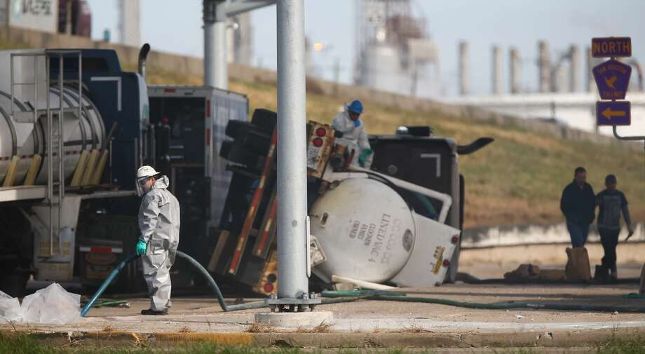 Authorities clean up hydrochloric acid that spilled from a truck that rolled over on the feeder road of Highway 225 eastbound, under Beltway 8, Thursday, Dec. 1, 2016, in Pasadena. ( Jon Shapley / Houston Chronicle ) Photo: Jon Shapley/ Houston Chronicle