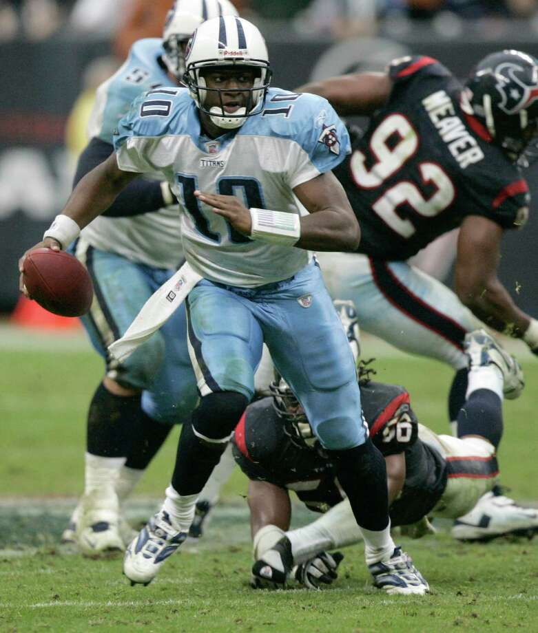Tennessee Titans quarterback Vince Young (10) steps out of the grasp of Houston Texans linebacker Morlon Greenwood on his way to a 39-yard touchdown run in overtime Sunday, Dec. 10, 2006, at Reliant Stadium in Houston.  The Titans beat the Texans 26-20 in overtime. (Photo by Brett Coomer / Houston Chronicle)