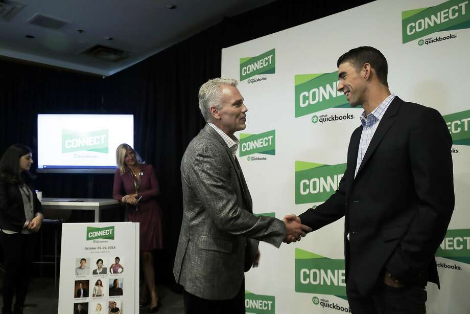 Former Olympic swimmer Michael Phelps shakes hands with Intuit Chairman and CEO Brad Smith. Photo: Marcio Jose Sanchez, Associated Press