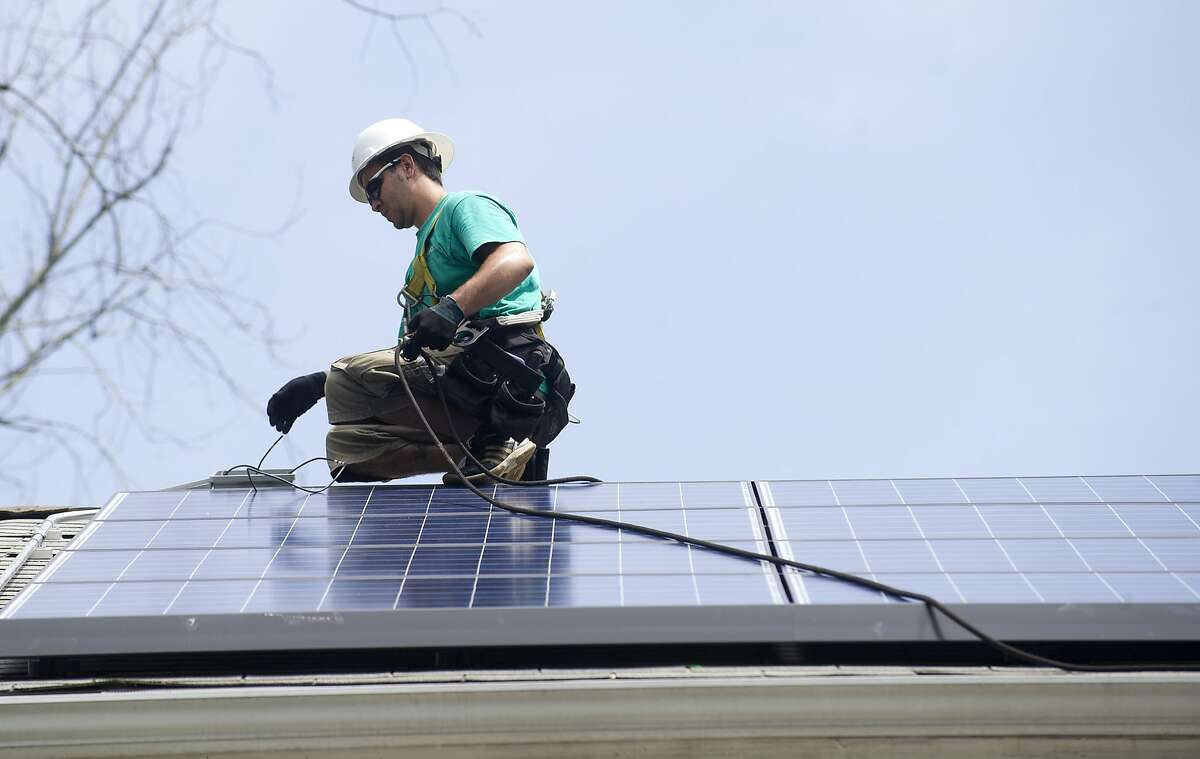Yohan Barrios of Solar City finishes installation of solar panels on a home in Greenwich, Conn., on Tuesday, July 9, 2013.