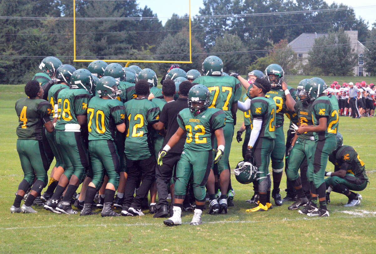 The Metro-East Lutheran/Madison football team huddles up before Week 1 action against Bunker Hill at MELHS.