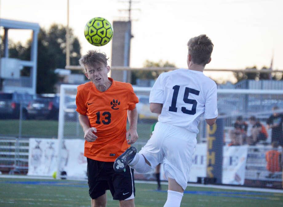 Edwardsville senior defender Sean Swanson, left, heads a ball away from an O'Fallon player during first-half action Thursday in O'Fallon.