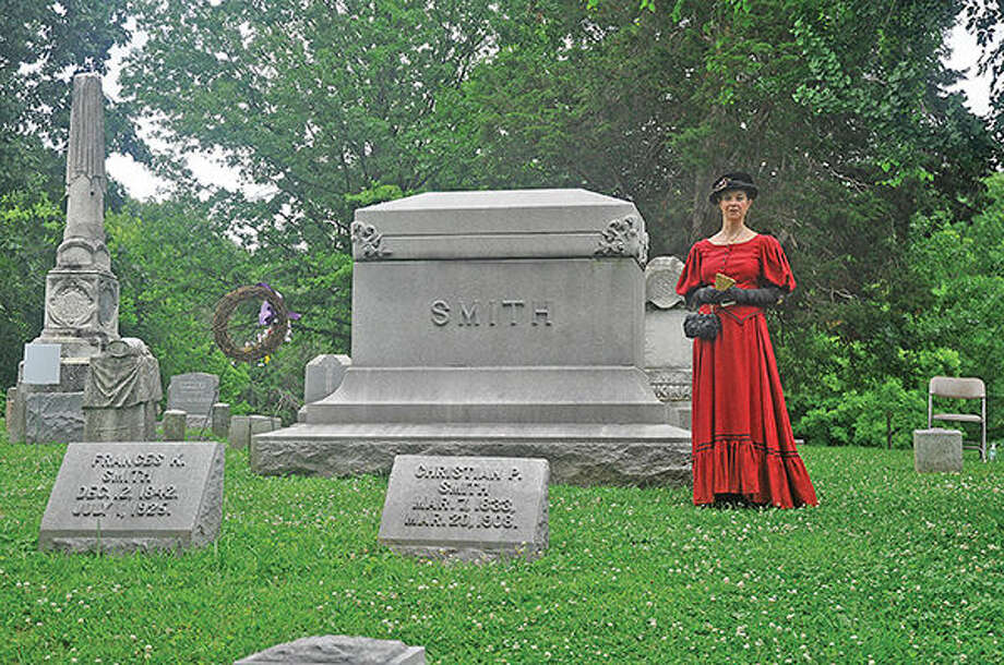 A Voices of the Past re-enactor stands on the Smith family plot at Woodlawn Cemetery.