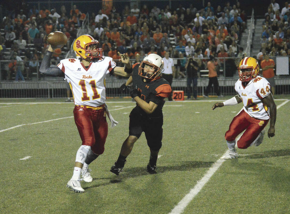 Edwardsville linebacker Sam Tilden, right, pressures Rock Island quarter Alek Jacobs in the second quarter of Friday's game at the District 7 Sports Complex.