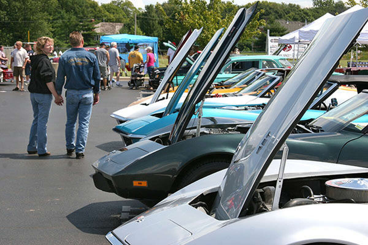 Showgoers peruse a line of cars at a previous DARE Car Show.