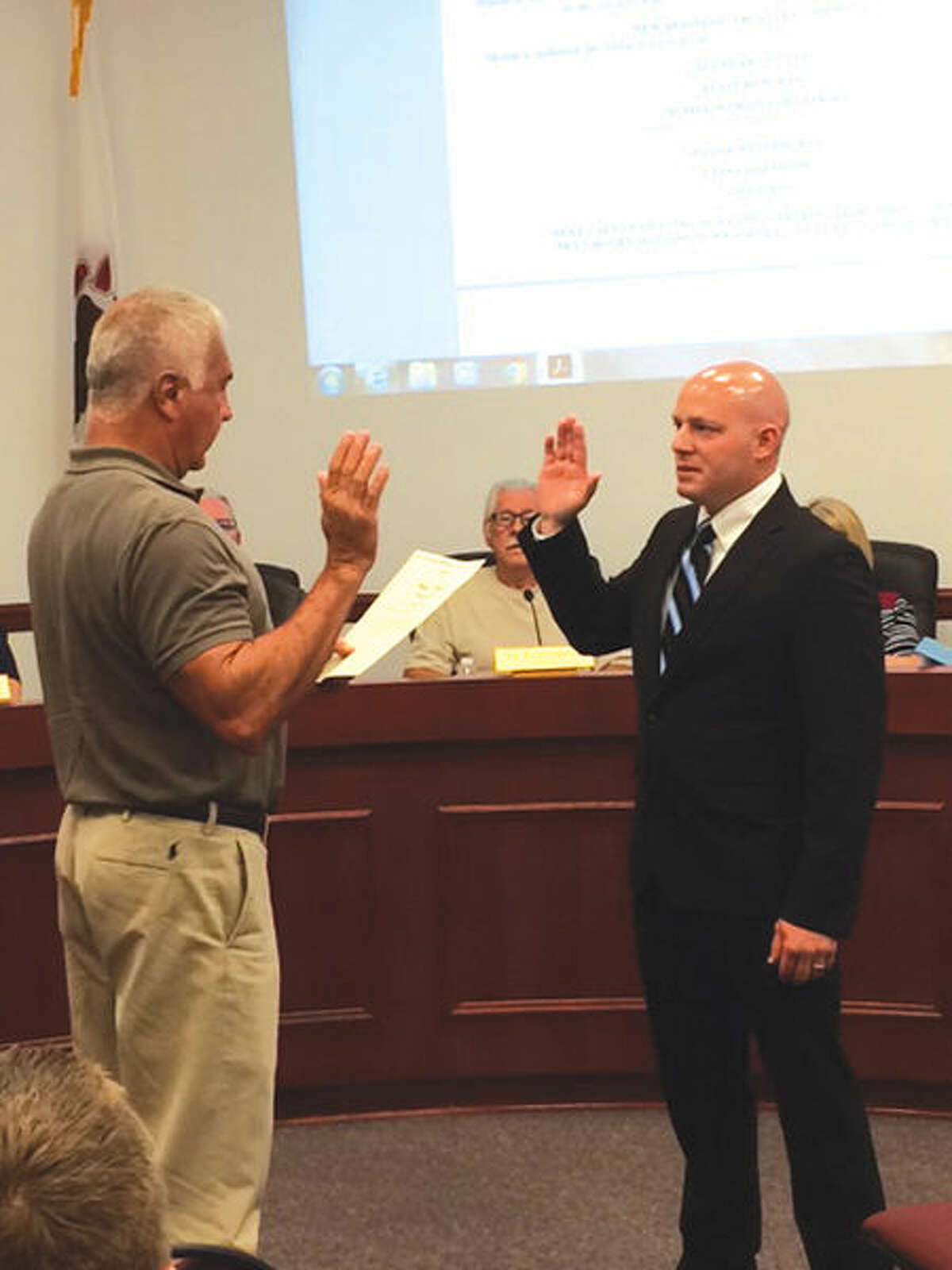 Gary Kukla, left, Chair of the Maryville Fire and Police Board of Commissioners, swears in new Maryville Police Officer Keith Mumper Wednesday.