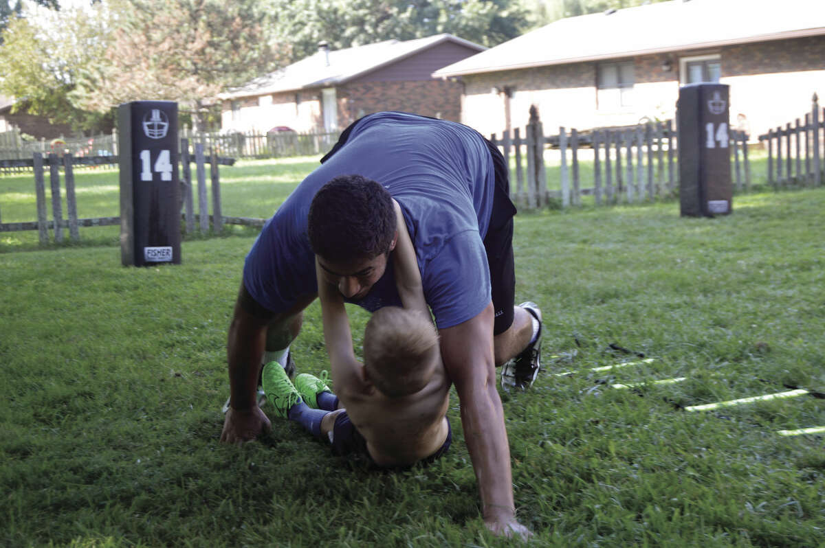 AJ Epenesa completes the military crawl with a younger kid hanging from his neck during the obstacle course race.