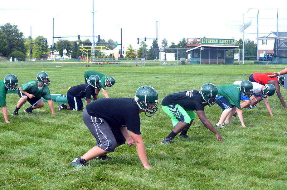 Metro-East Lutheran defensive linemen practice their stance during the team's first practice on Monday afternoon.