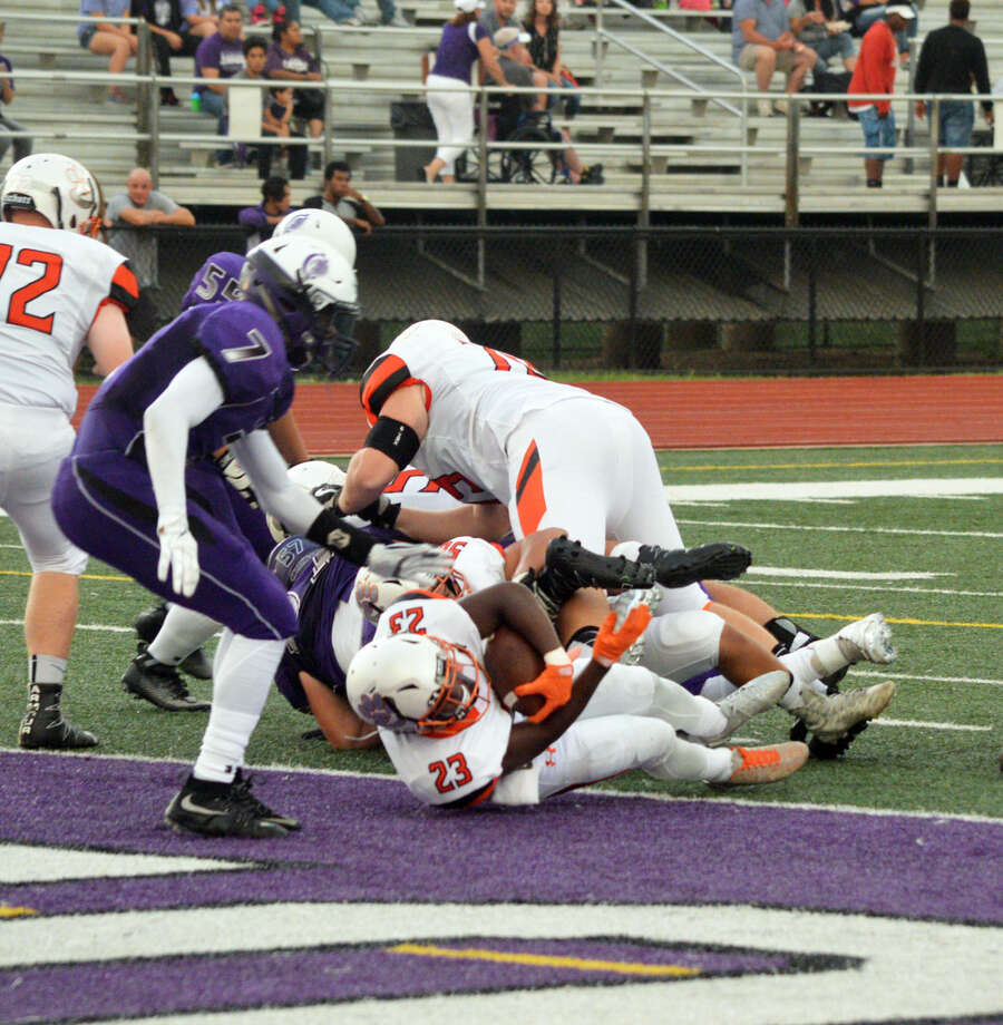Edwardsville running back Dionte Rodgers (No. 23) dives into the end zone for a touchdown early in the first quarter at Collinsville.
