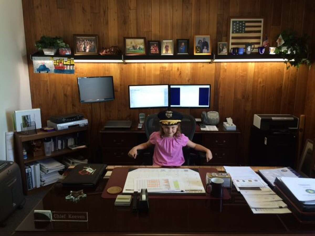 Laura Slater, 9, poses behind the police chief's desk as she takes on the job for a day. Slater received the opportunity after raising the most funds for the Ready, Set, Read program for grades 3 - 5.