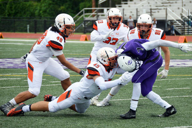 Edwardsville linebacker Andrew Holderer (No. 45) attempts to tackle Collinsville's Trevore Sanders with teammates Tyrese Brown (No. 48), Ryan Connelly (No. 33) and Nathan Kolesa (No. 88) alongside in the third quarter.