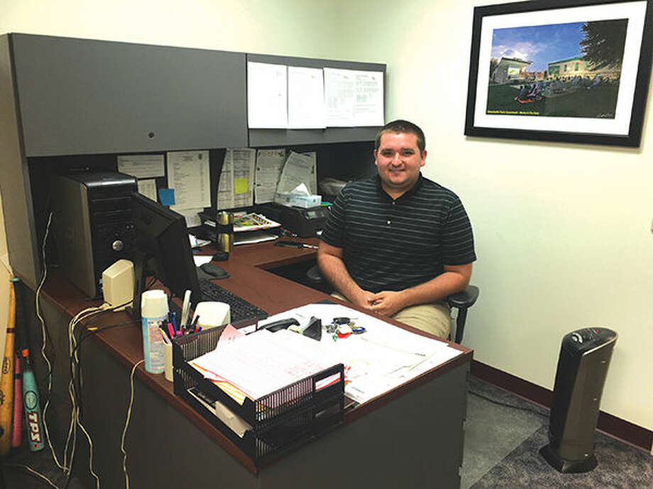 Brenton Ward poses behind his new desk as Edwardville's new sports supervisor.