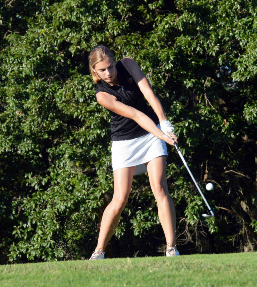 Edwardsville's Meara Schaefer hits an iron shot at the Highland Country Club on Monday during a triangular.