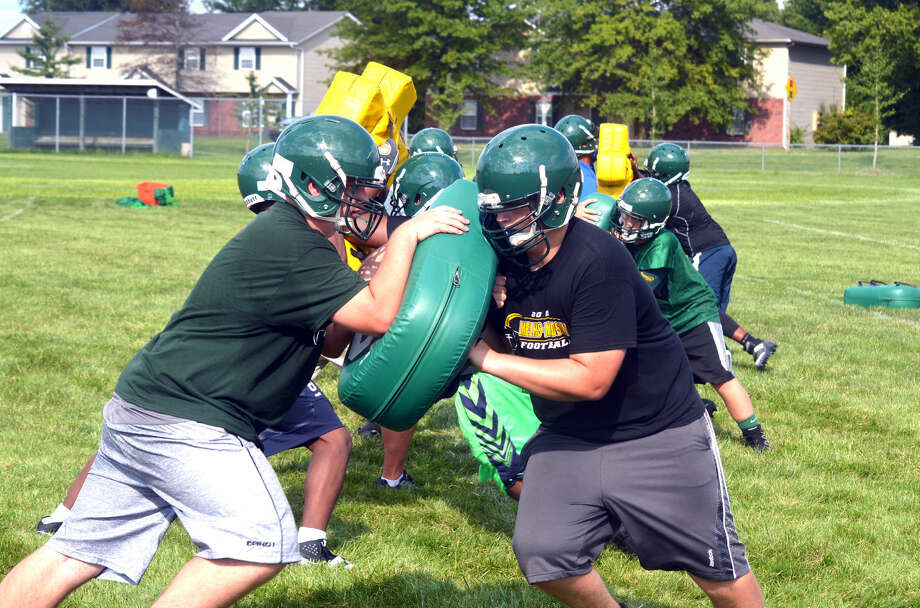Metro-East Lutheran football players perform a blocking drill on Monday during the team's first official practice session.