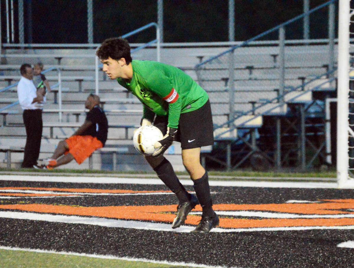 Edwardsville senior goalie Daniel Picchiotti scoops up a shot in the first half.