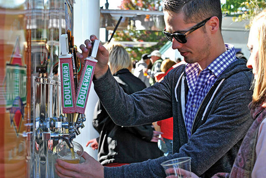 A booth worker pours a beer for a patron at a previous Global Brew Beer Fest in City Park.