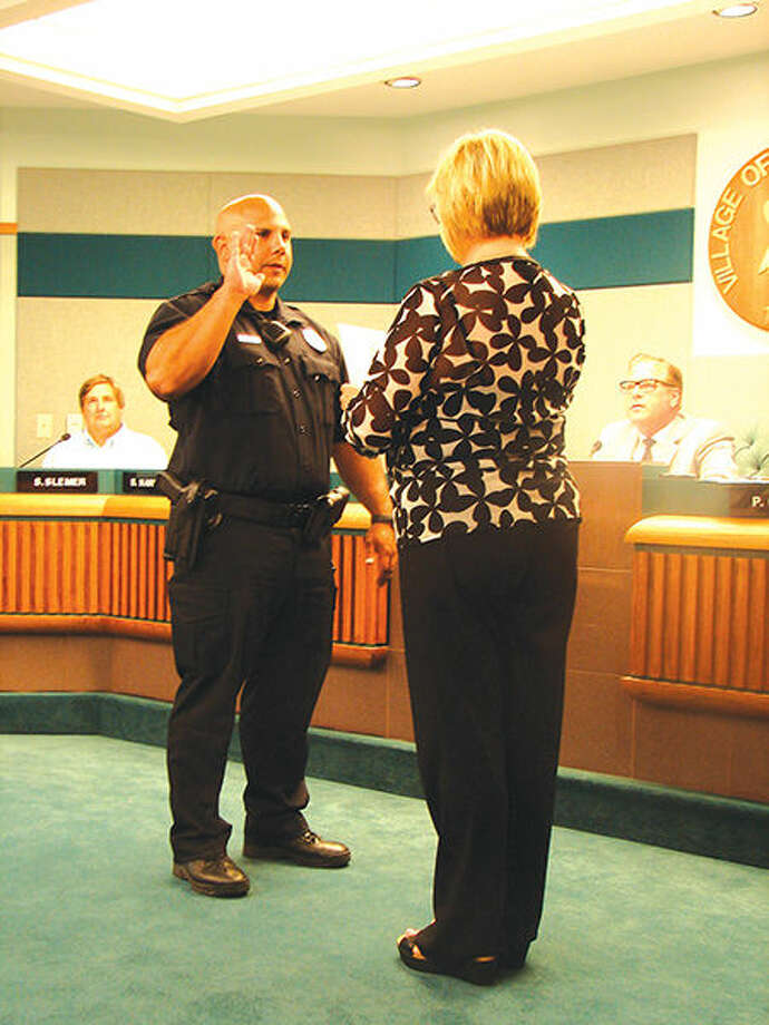Glen Carbon Village Clerk Peggy Goudy swears in new police officer Jeremy Coppotelli.