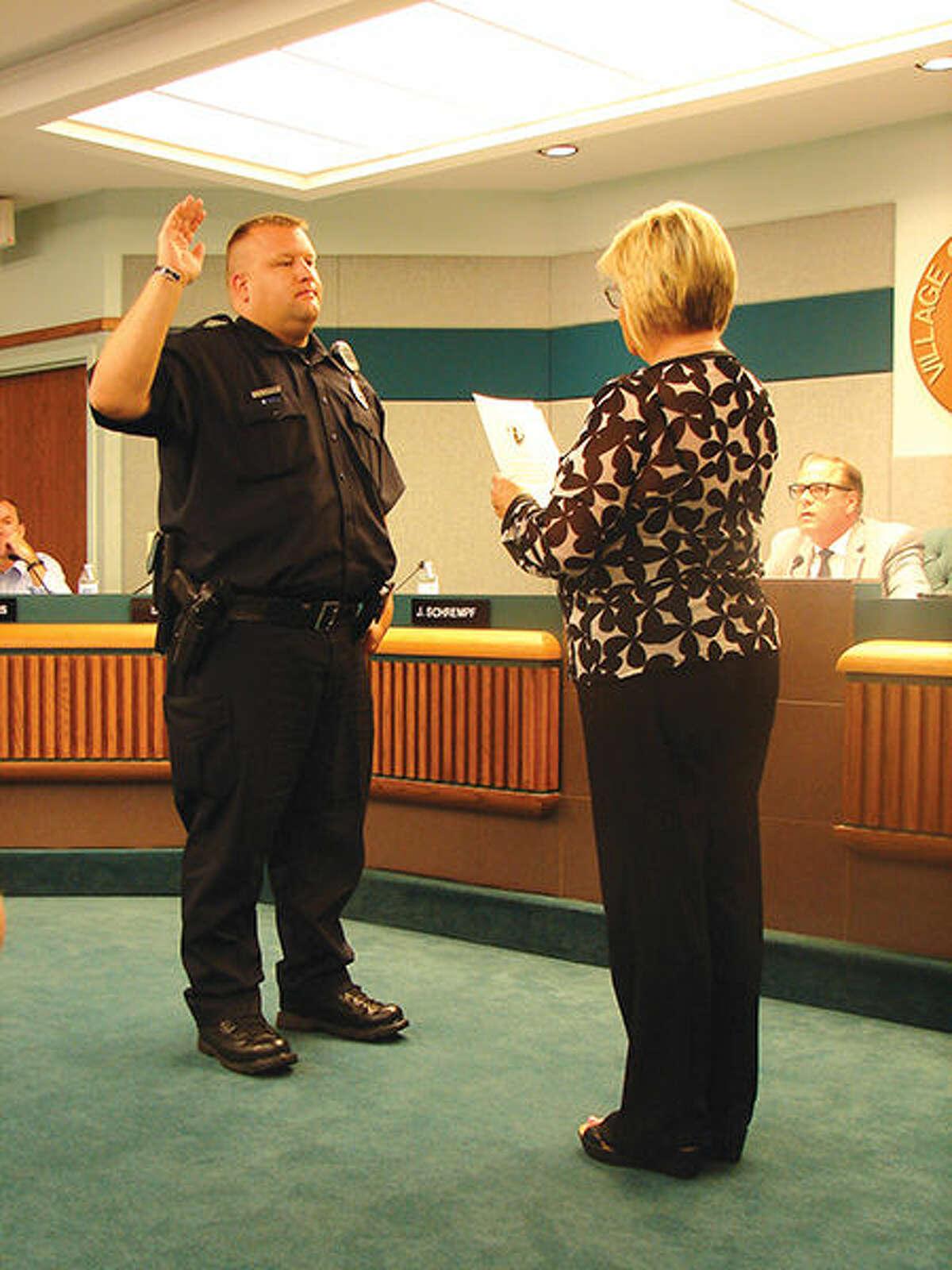 Glen Carbon Village Clerk Peggy Goudy swears in new police officer Jeffrey Hartsoe.