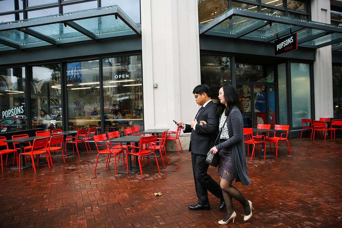 Pedestrians walk past Popsons Burgers after a rainstorm, on Market Street, in San Francisco, California, on Wednesday, November 30, 2016.