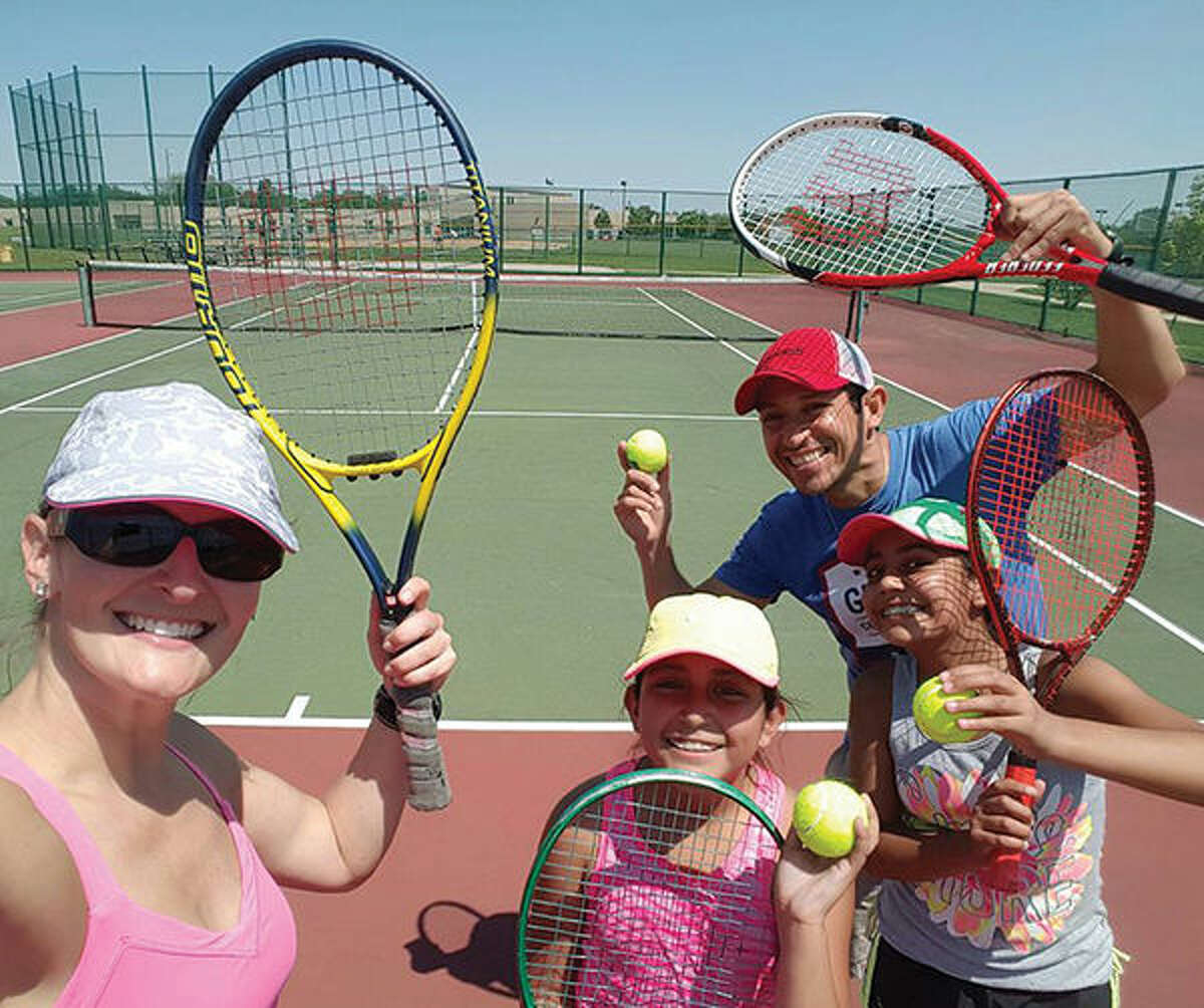 Paula Birke, Jorge Garcia and his two daughters take a break from tennis at Liberty Middle School.
