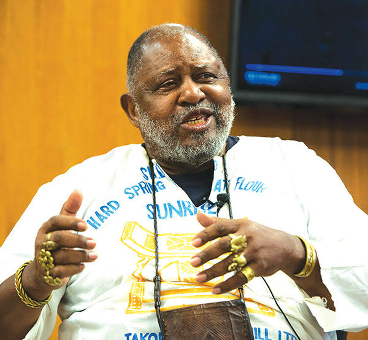 Ser Seshsh Ab Heter - C.M. Boxley speaks to an audience on Tuesday of mostly history course students. He is seen dressed in a white handmade tunic made out of flour sacks with images of the Sankofa bird on it.