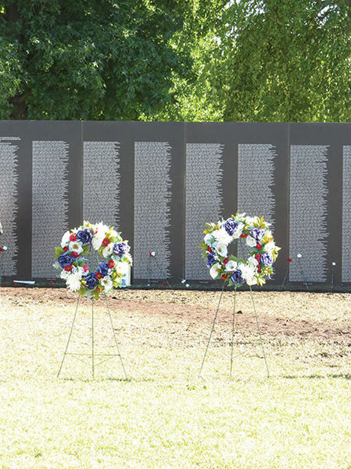 Wreaths honoring fallen military personnel stand in front of the traveling Vietnam Wall, which was in Troy recently.