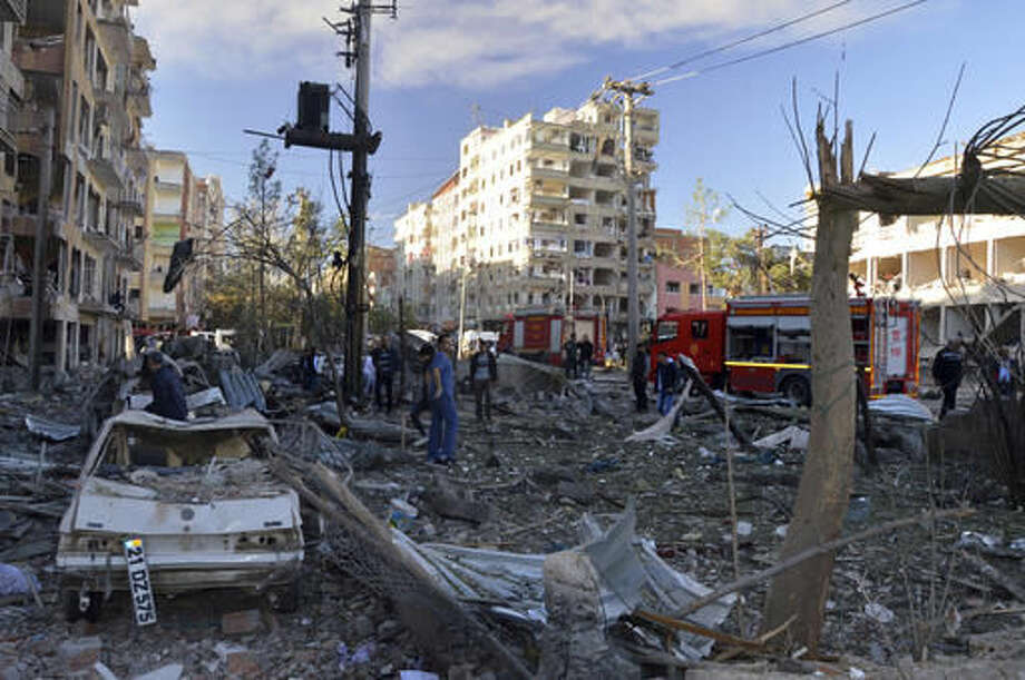 People watch the damage after an explosion in southeastern Turkish city of Diyarbakir, early Friday, Nov. 4, 2016. A large explosion hit the largest city in Turkey's mainly Kurdish southeast region on Friday, wounding several people, the state-run Anadolu Agency reported. The cause of the explosion was not immediately known but Hurriyet newspaper said it may have been caused by a car bomb. (IHA via AP)