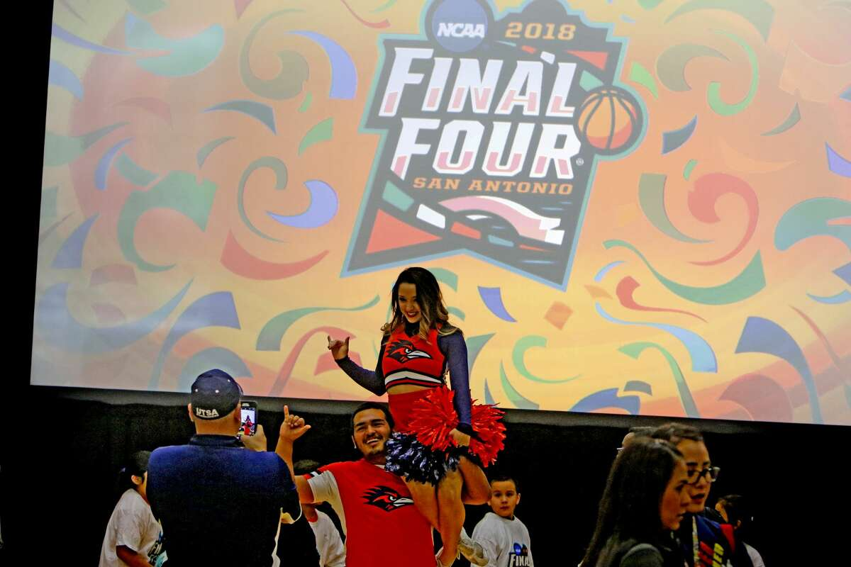 UTSA cheerleaders Alex Tello and Nataly Navarro have their photo taken in front of the final four logo at the Final Four Logo Unveiling & Pep Rally Kick Off Road to San Antonio. The NCAA and San Antonio Local Organizing Committee (SALOC) will unveil the logo for the 2018 Men?•s Final Four¨ before 1,000 elementary students, dignitaries and special guests. The UTSA band and cheerleaders will also participate. The unveiling kicks off 18 months of preparation as San Antonio gets ready to host this premier sports event. Thursday, December 1, 2016 at Mission Conception Sports Gym.